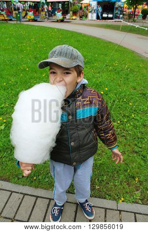 Funny boy eating cotton candy at the park