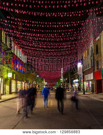 MONTREAL CANADA - 17TH MAY 2015: A view along Saint Catherine Street in Montreal at night showing businesses and the blur of people.