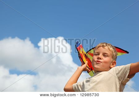 boy plays kite against sky