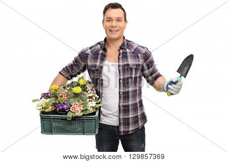 Young male gardener holding a rack of flowers and a spade isolated on white background