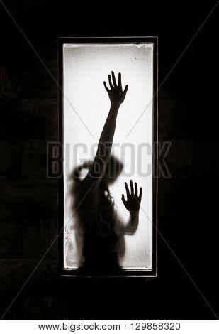 Shadowy figure behind glass.  Dramatic film grain