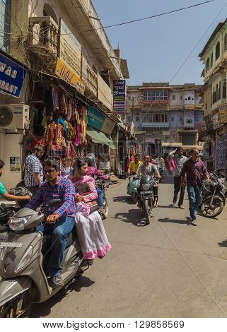 UDAIPUR INDIA - 21ST MARCH 2016: Streets scenes in Udaipur India during the day. Showing people motorbikes shops and building exteriors.