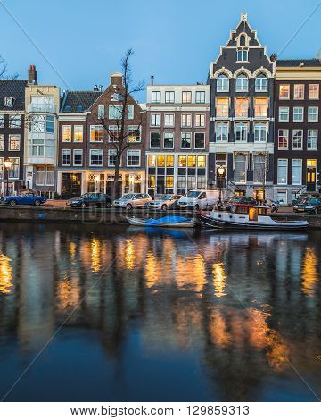 AMSTERDAM NETHERLANDS - 16TH FEBRUARY 2016: A view along the Amsterdam Canals at twilight. Buildings people cars and boats can be seen.