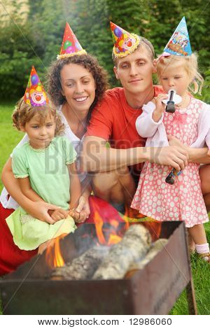 Happy family with children near brazier on picnic, happy birthday party seven years