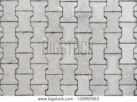 Concrete or cobble gray H Shaped pavement slabs or stones for floor wall or path. Traditional fence court backyard or road paving.
