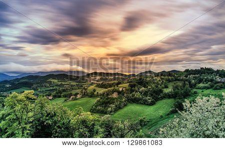 Urbino hills landscape at sunset. Cloudscape dramatic sky