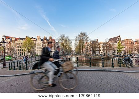 People bicycling through city streets on a beautiful sumer day in Amsterdam Netherlands