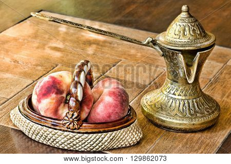 Retro arabian style brass coffee pot and ceramic vase with peaches on a table.Soft toned image.