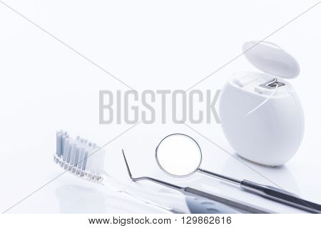 Dental Floss And Brush With Basic Dental Tools On A White Table