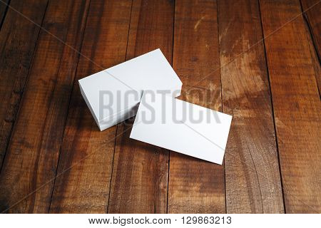 Blank business cards. Photo of blank business cards on vintage dark wooden background. Template for ID. For design presentations and portfolios.