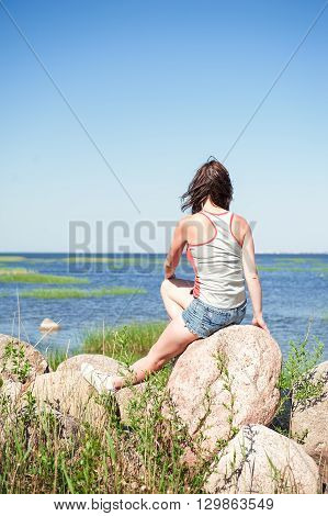 Young Dreaming Woman Sitting On The Rock Facing The Sea