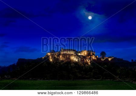 Stirling Castle floodlit at night with a full moon.