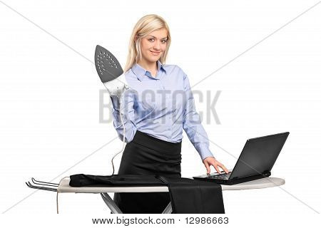 Young Businesswoman Ironing His Clothes And Working On A Laptop