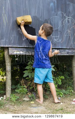 Child boy wiping blackboard in outdoor forest school clasroom education concept.