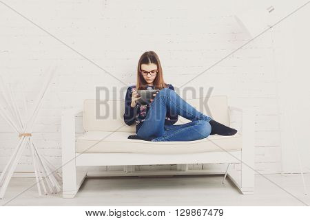 Teenager girl relax home, sitting on sofa with tablet computer. Child wears glasses, eyeglasses. Girl in eyewear with gadget tablet pc sits on sofa. Adolescence, internet addiction. High key