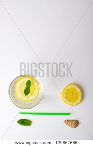 Flat lay ingredients for homemade lemonade. Lemon lime ginger and mint for refresh water lay in white background.