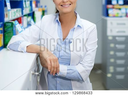 Beautiful young woman pharmacist standing at her workplace in pharmacy.