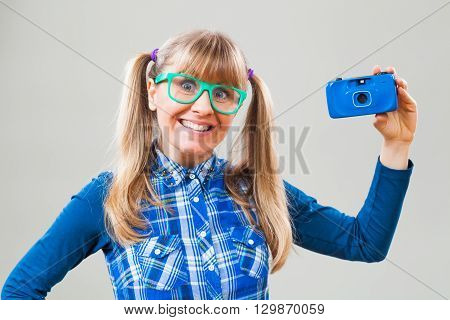 Studio shot portrait of happy nerdy woman who is holding photo camera