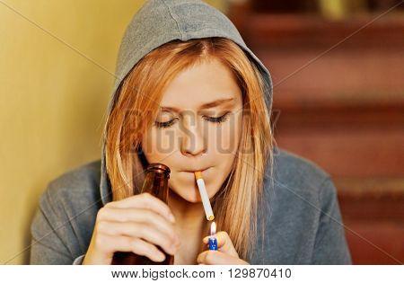 Teenage woman drinking beer and smoking cigarette