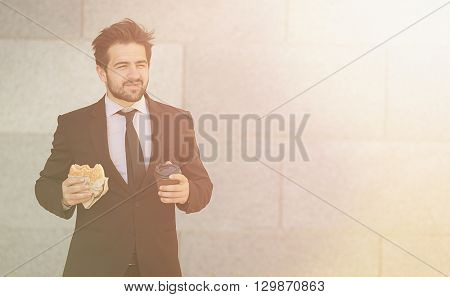 Toned picture of young businessman eating junk food and drinkig tea or coffee while walking to office along street.
