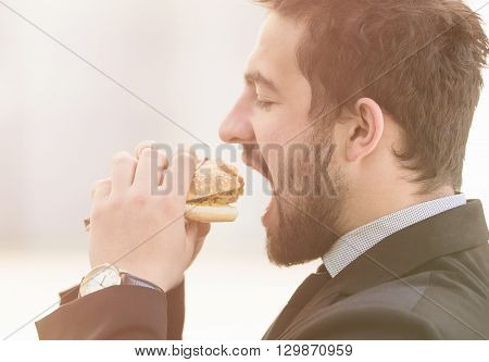 Closeup toned image of businessman eating junk food on street. Freelance man in business suit having snack before work.