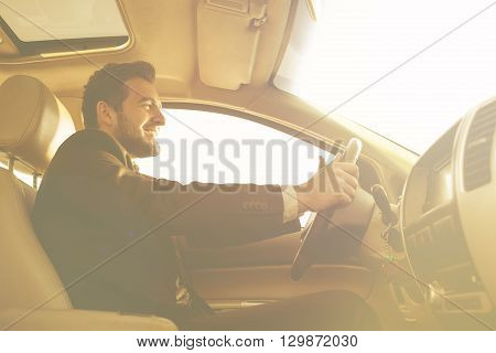 Toned picture of smiling businessman driving car to work. Freelance man in black business suit looking in front of him.