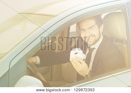 Toned picture of happy businessman in black business suit eating doughnut while driving car to his office. Freelance man smiling for camera.