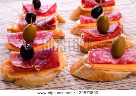 Sandwiches with sausage and jamon. On a light background.