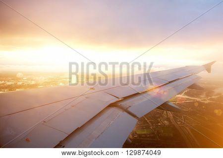 Airplane Wing Descending Through The Clouds At Sunset
