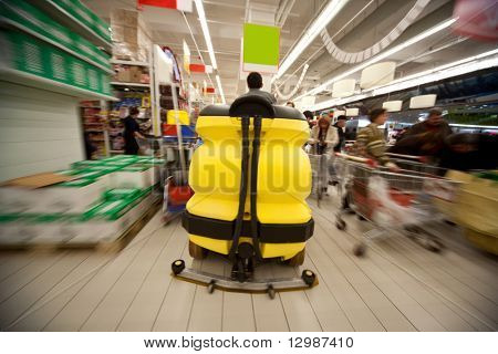 Motion blur of yellow clean machine in center of trading floor in supermarket
