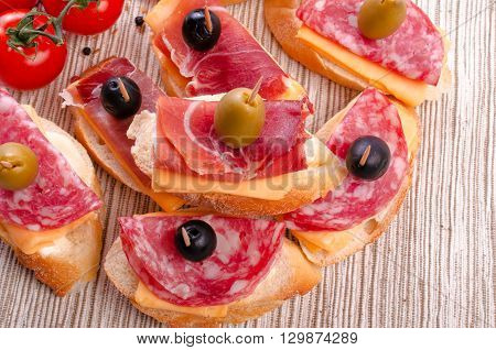 Sandwiches with sausage jamon and spices. On a light background.