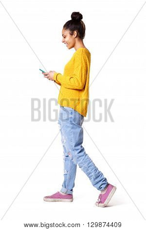 Smiling Young Woman Walking And Looking At Mobile Phone