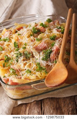 Austrian Noodles Baked With Ham And Parmesan Close-up In A Glass Baking Dish. Vertical