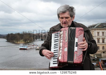 Prague, Czech Republic - March  28, 2015: Elderly man plays the accordion on the Charles Bridge on March  28, 2015 in Prague, Czech Republic