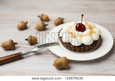 Cake with cream and cherry on the acorns on the table