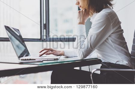Working Process in Modern Office. Young Woman Account Manager Working at Wood Table with New Business Project. Typing keyboard, Using Contemporary Laptop. Horizontal. Film effect. Blurred background.