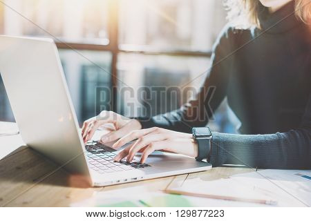 Work Process in Modern Office. Young Account Manager Working at Wood Table with New Business Project.Typing Contemporary Laptop keyboard, Wearing Smartwatch. Horizontal. Film effect.Blurred background.