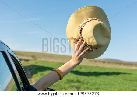 Woman Hand With A Hat Through Car Window.