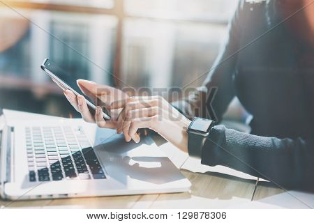 Photo Woman Working Modern loft, Wearing Generic Design Smart Watch.Female Hands Touching screen Mobile Phone.Manager Work Process.Laptop on the wood Table.Horizontal, Burred background. Film effects.