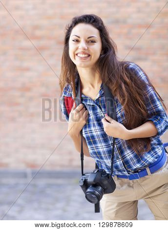 Outdoor summer smiling lifestyle portrait of pretty young woman having fun in the city in Europe in evening with camera. Travel photo of photographer