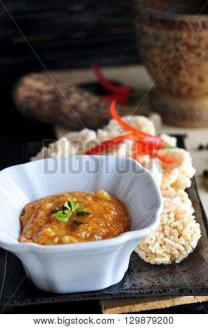 Thai style dip sauce with rice cracker with mortar on background