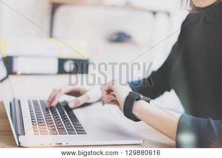 Photo Girl Working Modern Laptop in Studio Loft. Woman Looking at Screen Generic Design Smartwatch.Manager Work Process.Laptop on the Wood Table.Horizontal, Burred background. Film effect.