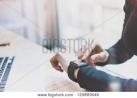 Photo Woman Working Modern loft, Using Generic Design Smart Watch.Female Hands Touching Screen Smartwatch.Account Manager Work Process. Horizontal mockup, Burred background. Film effects.