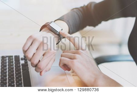 Photo Woman Working Modern loft, Using Generic Design Smart Watch.Female Finger Touching Screen Smartwatch.Account Manage Work Process. Horizontal. Burred background. Film effects.