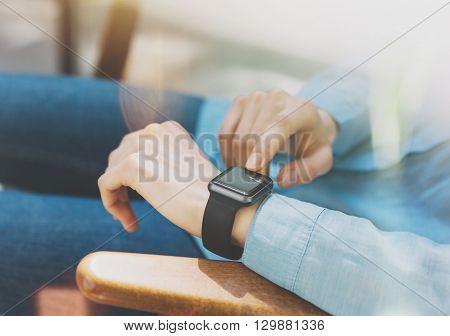 Photo Woman Relaxing Modern Loft Studio.Girl Enjoying Generic Design Smart Watch.Female Hands Touching Screen Smartwatch.Free Time Management. Horizontal. Burred background. Film effects.