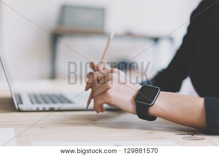 Photo Girl Working Modern Laptop in Studio Loft. Woman Wearing Generic Design Smartwatch.Account Manager Work Process. Notebook on the Wood Table.Horizontal mockup.Burred background. Film effect.