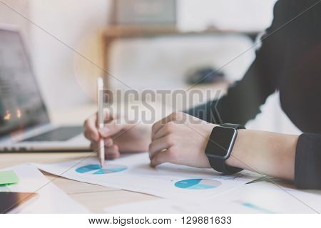 Photo Woman Working Modern Office.Girl Wearing Generic Design Smart Watch.Female Hands Writing notes. Account Manager Work Process at Wood Table.Horizontal mockup.Burred Background. Film effect.