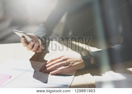 Photo Woman Working Modern Office.Girl Wearing Generic Design Smart Watch.Female holding smartphone hands. Account Manager Work Process at Wood Table.Horizontal mockup.Burred Background. Film effect.