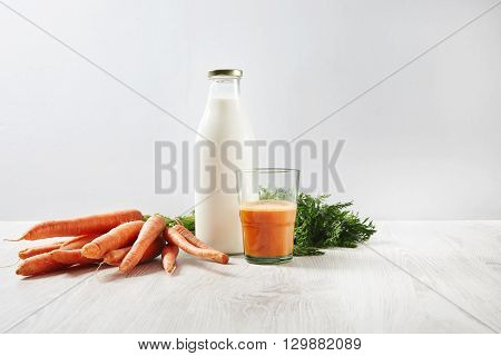 Organic Farm Carrot Harvest Lying Near Bottle With Milk And Glass Half Filled With Natural Fresh Jui