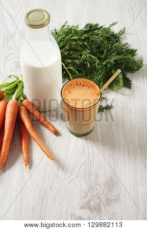 Farm Carrot Harvest Lying Near Milk Bottle And Glass Filled With Mix Natural Fresh Juice And Milk Wi